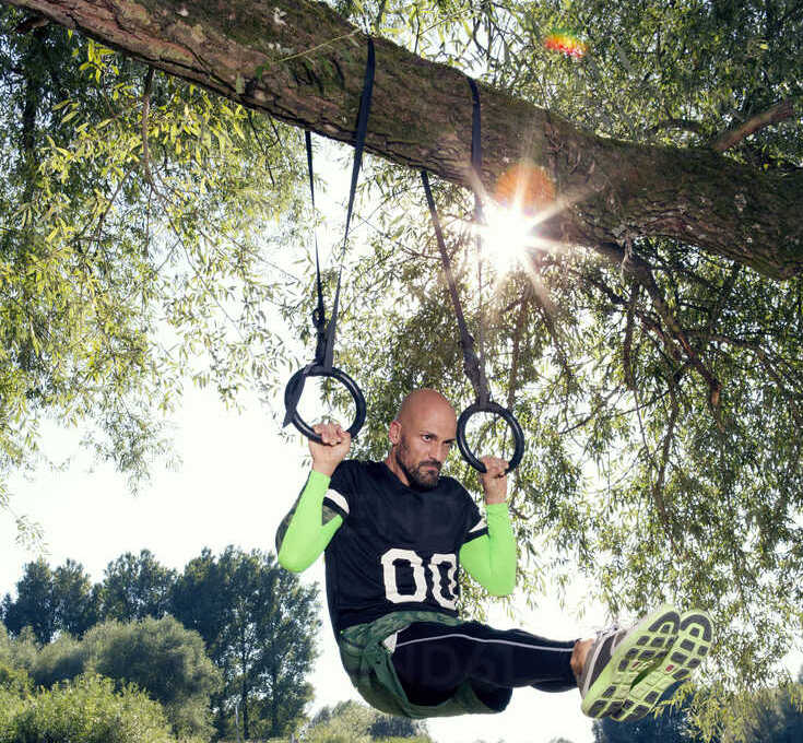 Man doing CrossFit exercise on rings hanging on tree trunk