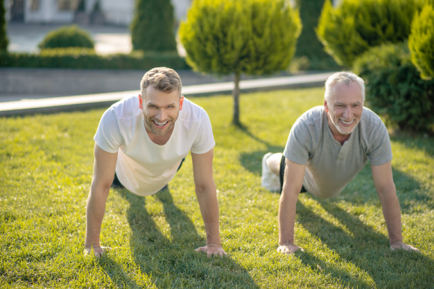 Dad and son doing push ups on grass
